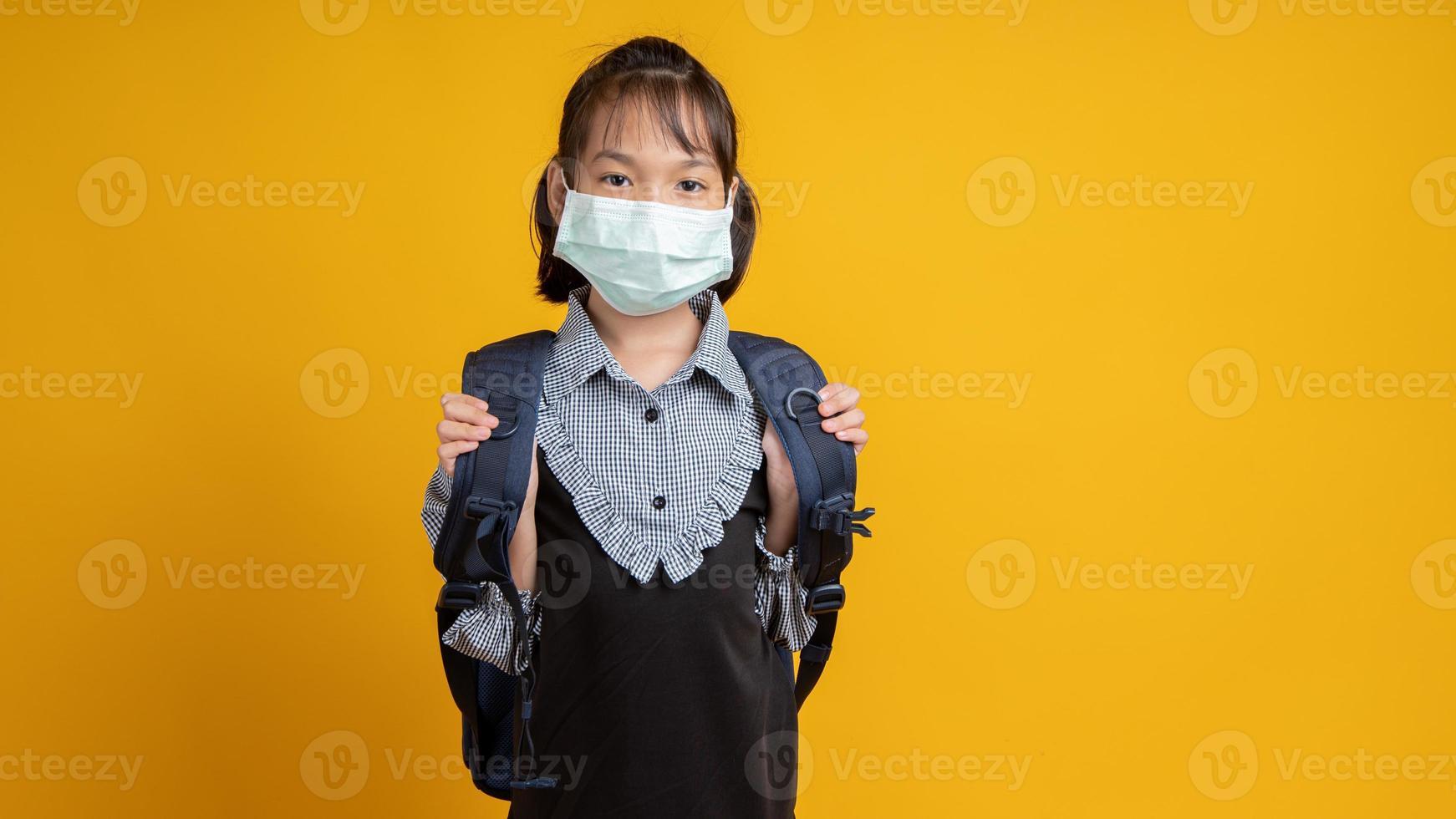 menina asiática usando máscara facial com mochila olhando para a câmera com fundo amarelo foto