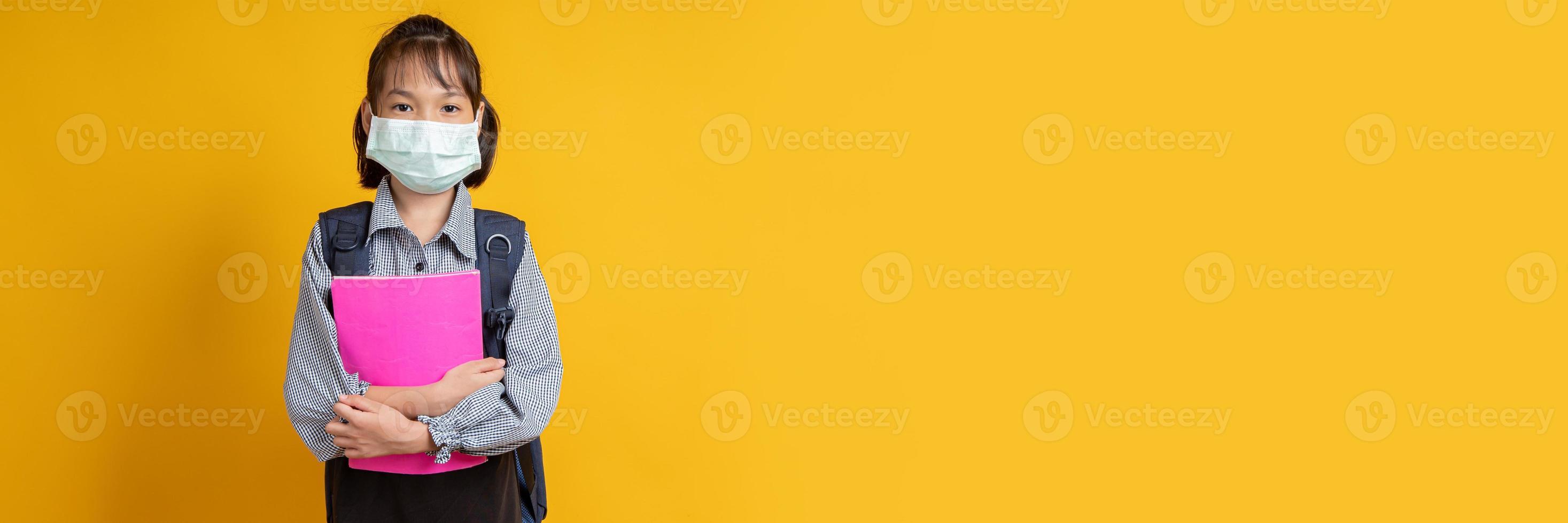 menina asiática usando máscara facial usando mochila e segurando livros olhando para a câmera com fundo amarelo foto