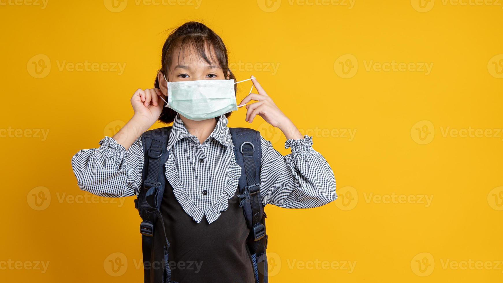 jovem asiática usando uma máscara facial e mochila olhando para a câmera com fundo amarelo foto