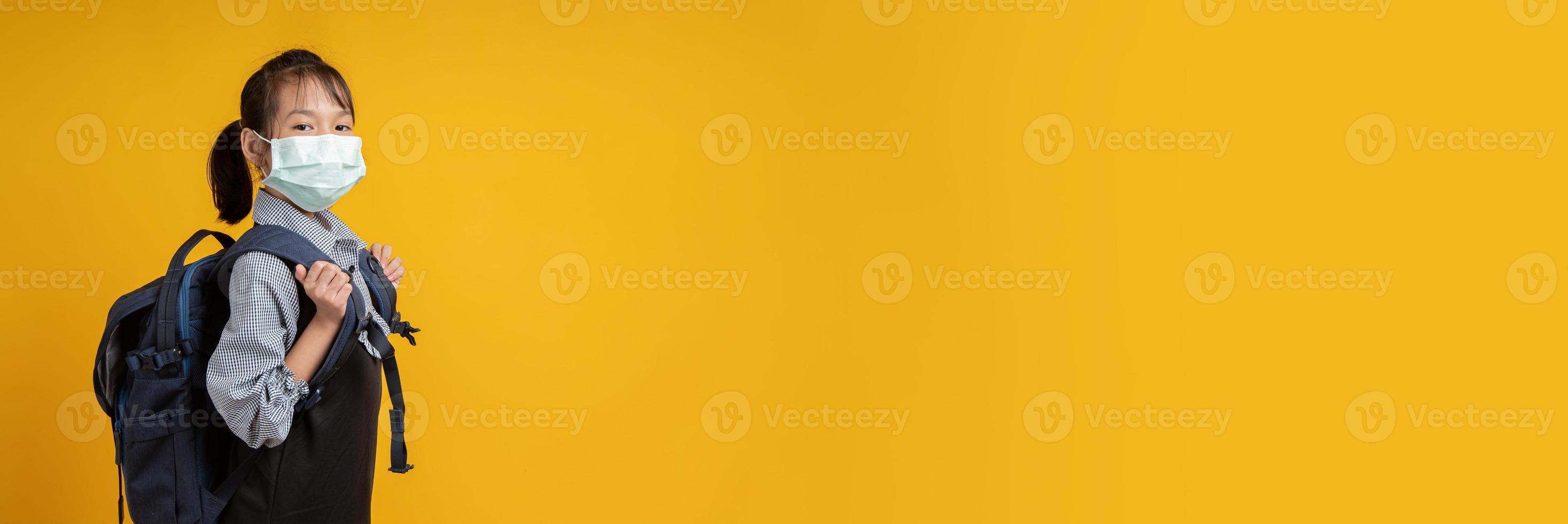 jovem tailandesa usando uma mochila e olhando a câmera com fundo amarelo foto