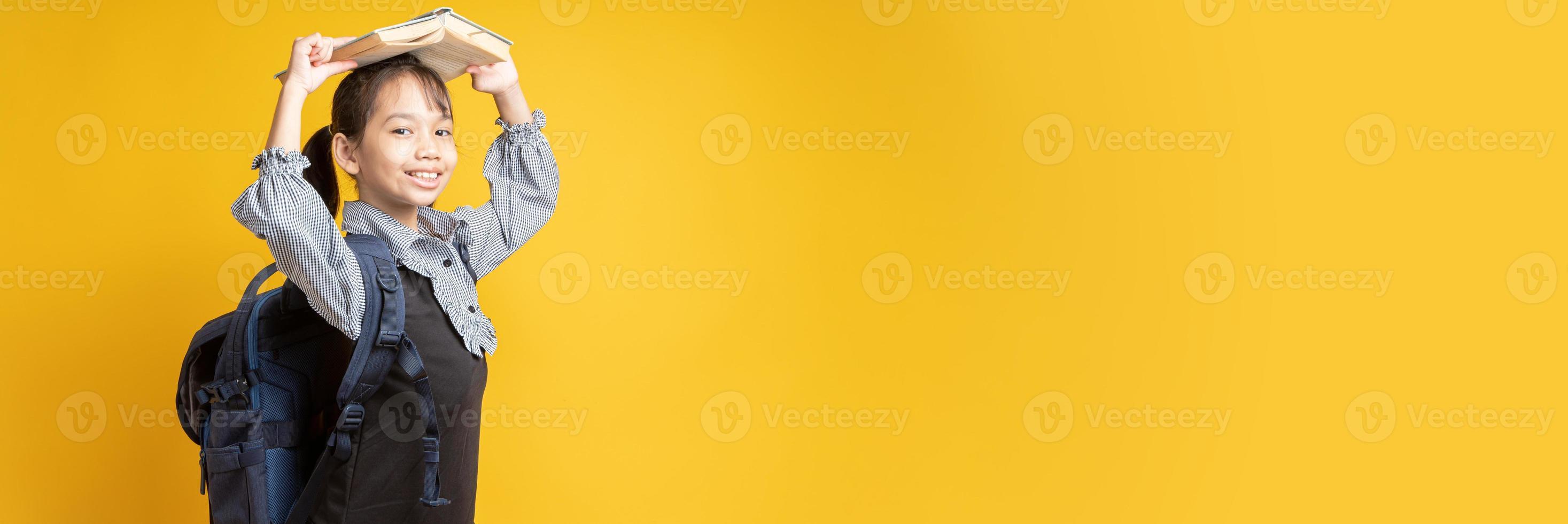 jovem tailandesa usando mochila e segurando um livro na cabeça, olhando para a câmera com fundo amarelo foto