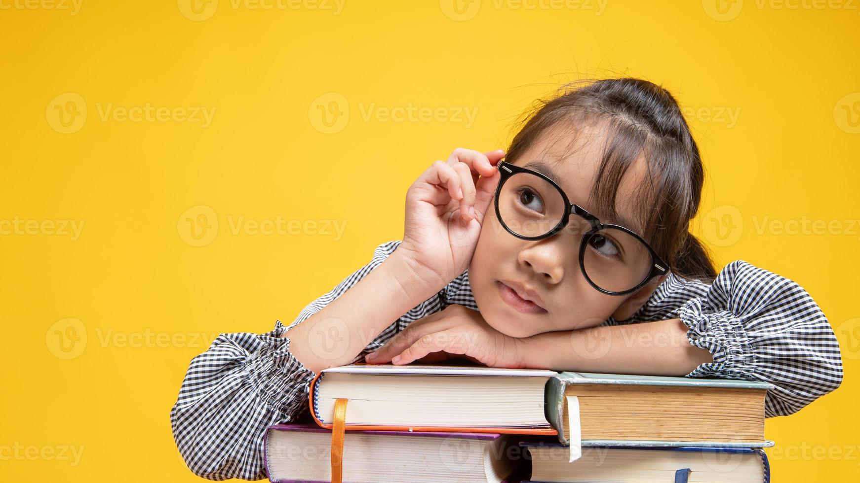 jovem tailandesa encostada na pilha de livros, tocando seus óculos e pensando em estúdio com fundo amarelo foto
