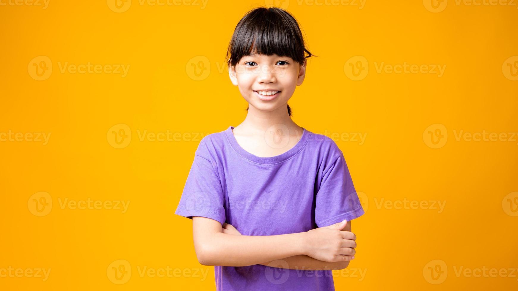 jovem asiática de camisa roxa sorrindo com os braços cruzados no estúdio com fundo amarelo foto