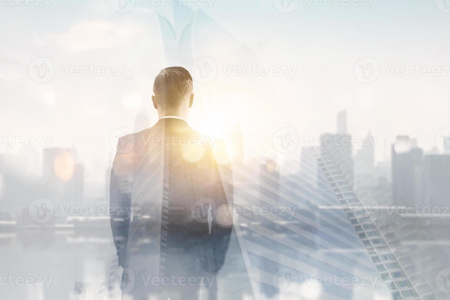 dupla exposição das costas do homem de terno olhando o horizonte da cidade e a luz do sol foto