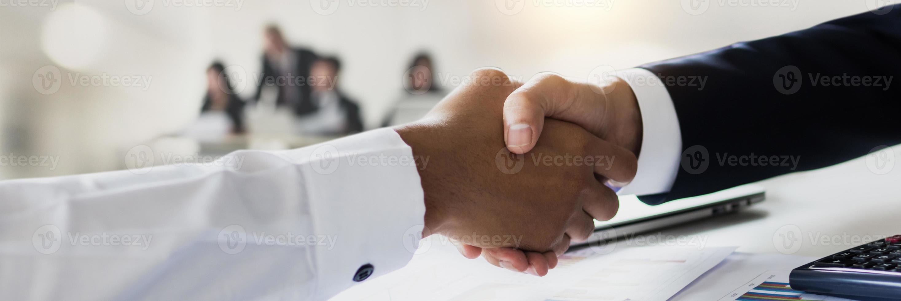close-up de empresários apertando as mãos de pessoas desfocadas ao fundo foto