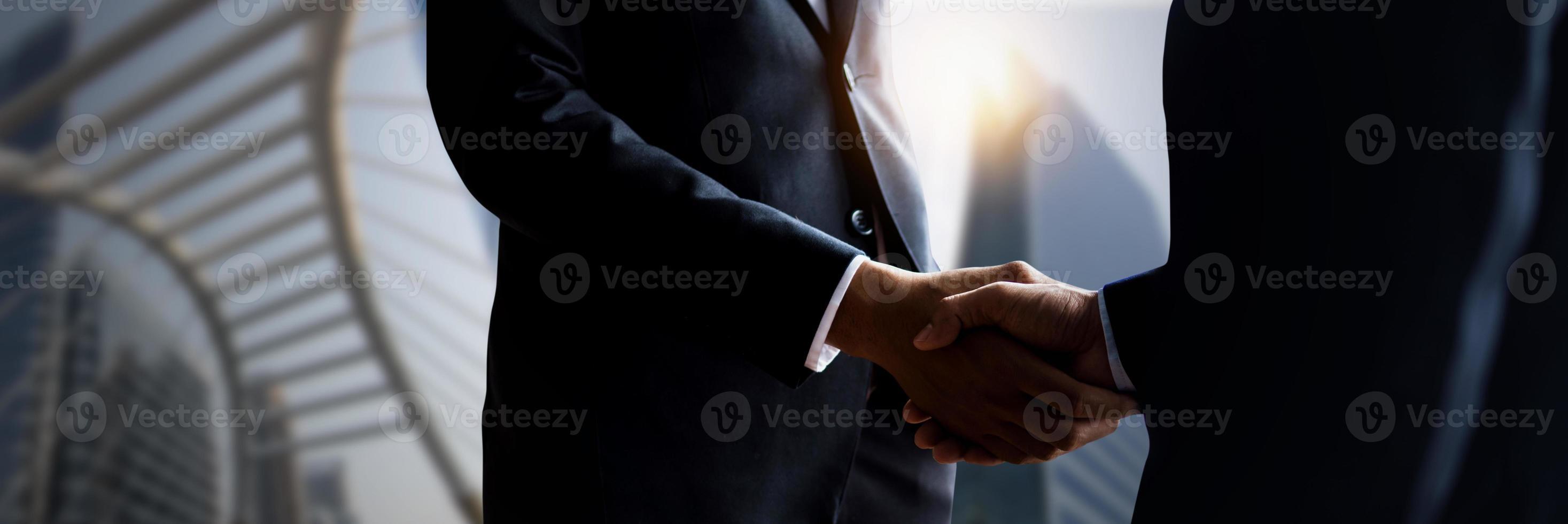 close-up de empresários apertando as mãos com edifícios desfocados da cidade ao fundo foto