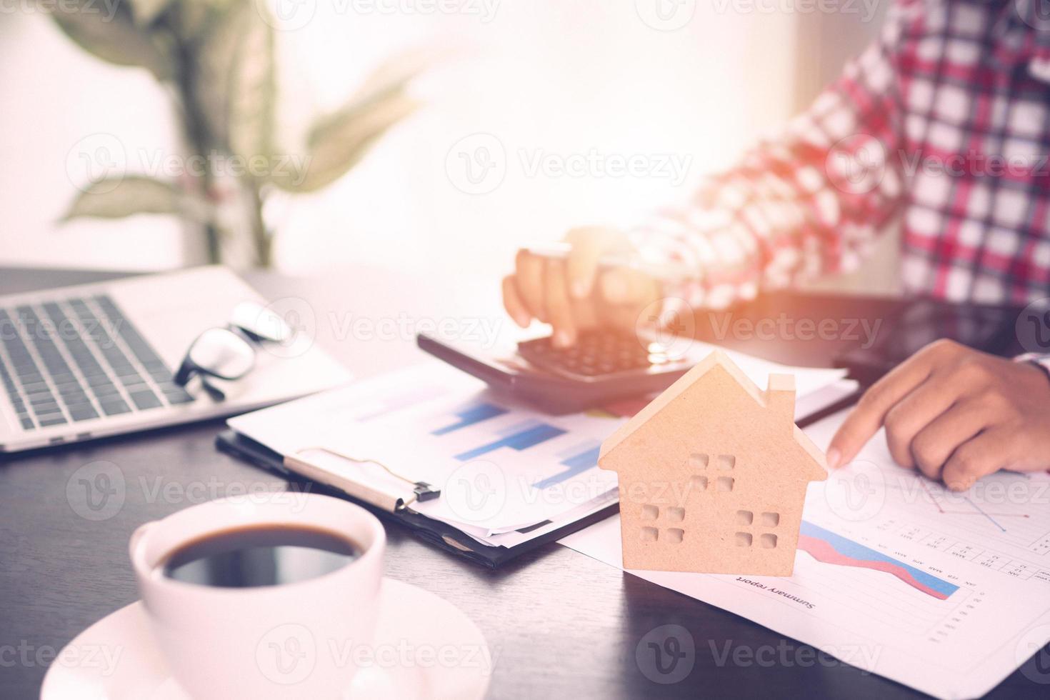modelo com calculadora, modelo de casa, laptop, café e papéis de tabelas e gráficos foto
