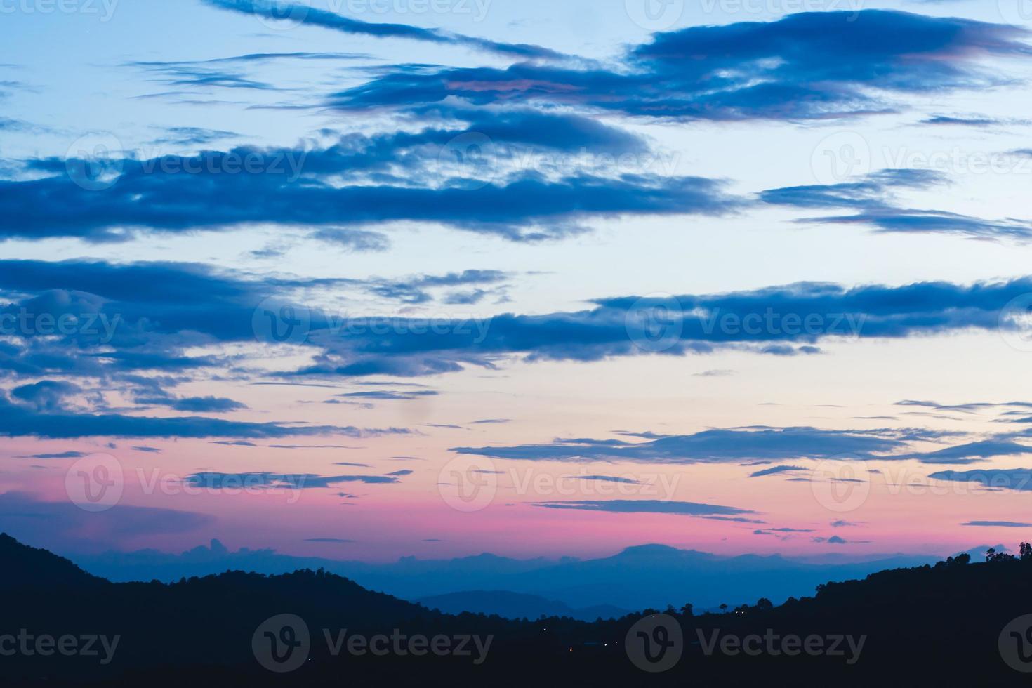pôr do sol nublado colorido sobre árvores e montanhas foto