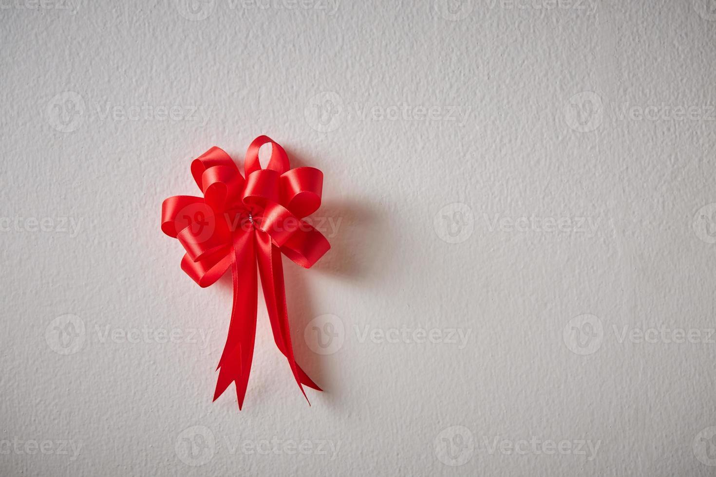 fita vermelha em uma parede de textura branca foto