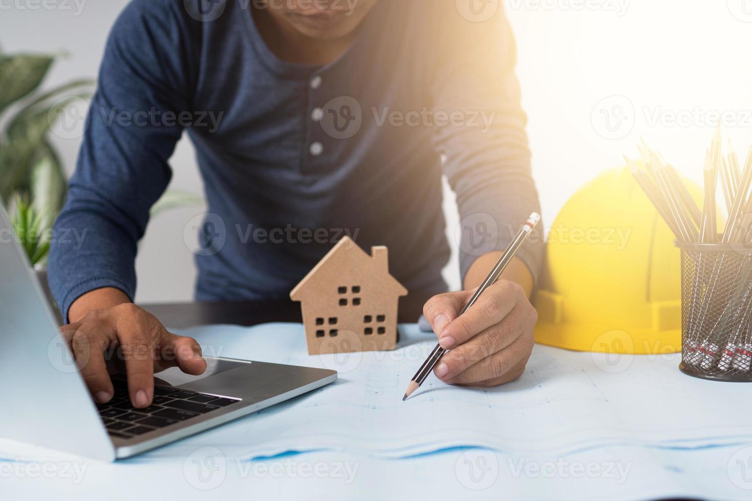 arquiteto trabalhando em um projeto ao lado do laptop, capacete, lápis e modelo de casa foto