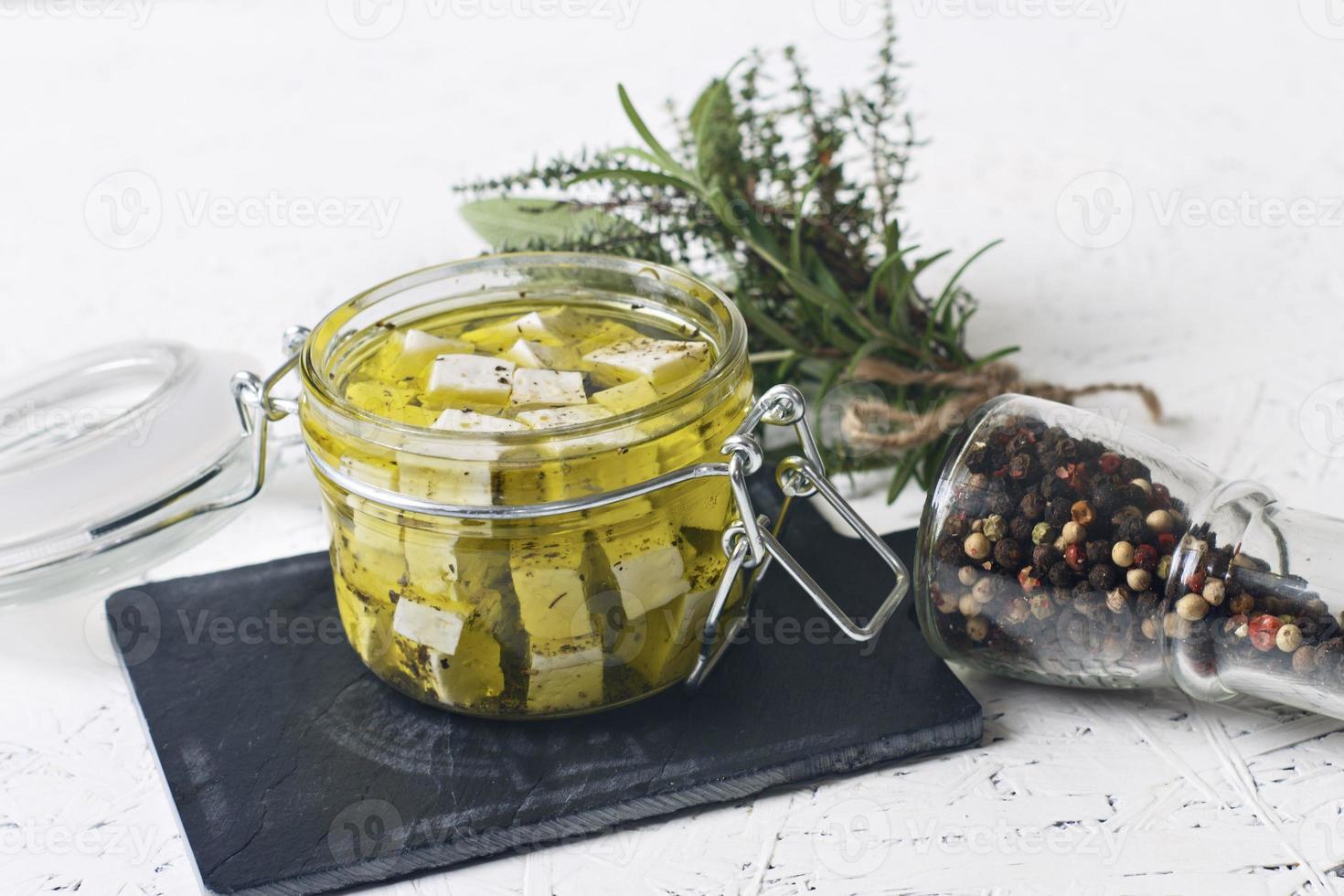 queijo feta marinado em uma jarra de vidro e especiarias sobre um fundo branco foto