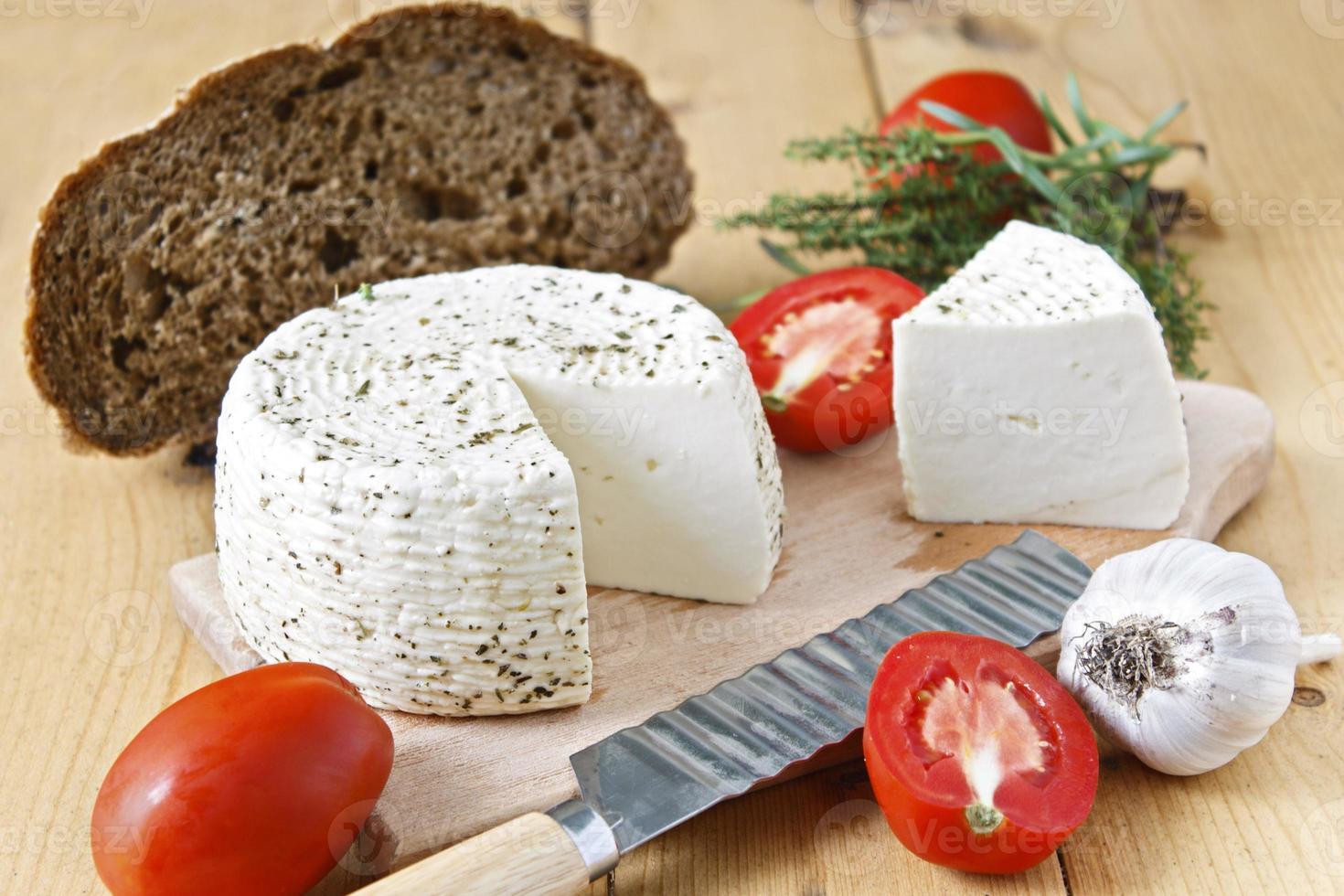 queijo branco, pão, tomate e alho em um fundo de madeira foto