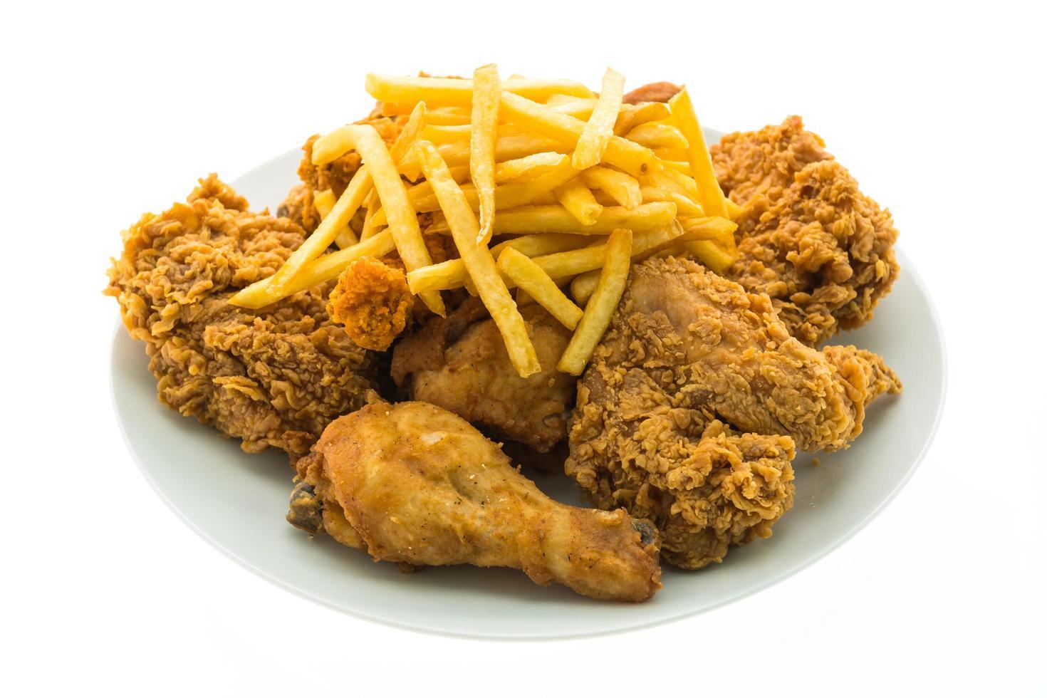 frango frito e batatas fritas em um prato branco foto