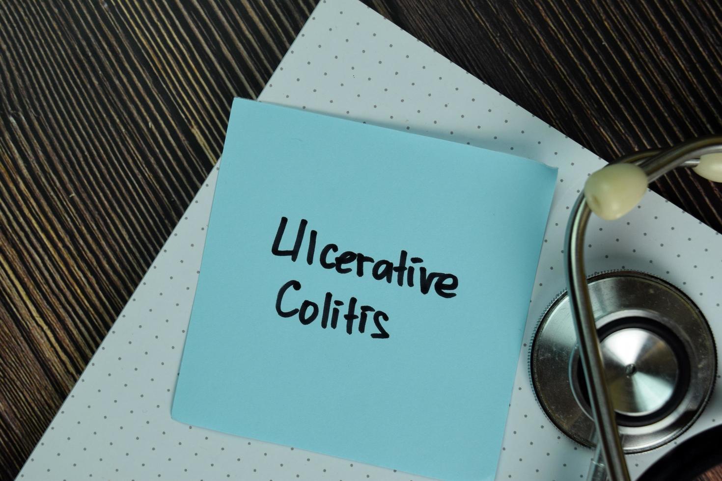 colite ulcerosa escrita em nota auto-adesiva isolada na mesa de madeira foto