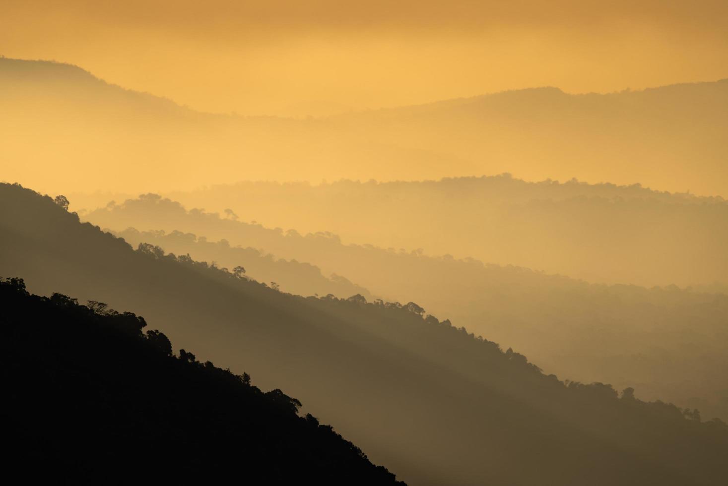 silhuetas de montanhas ao pôr do sol foto