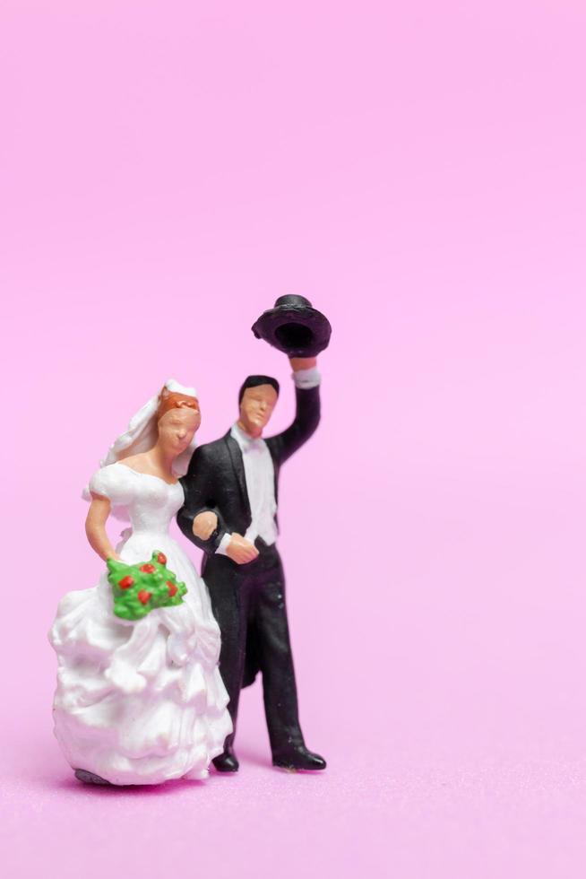noiva e noivo em miniatura em um fundo rosa, dia dos namorados e conceito de casamento foto