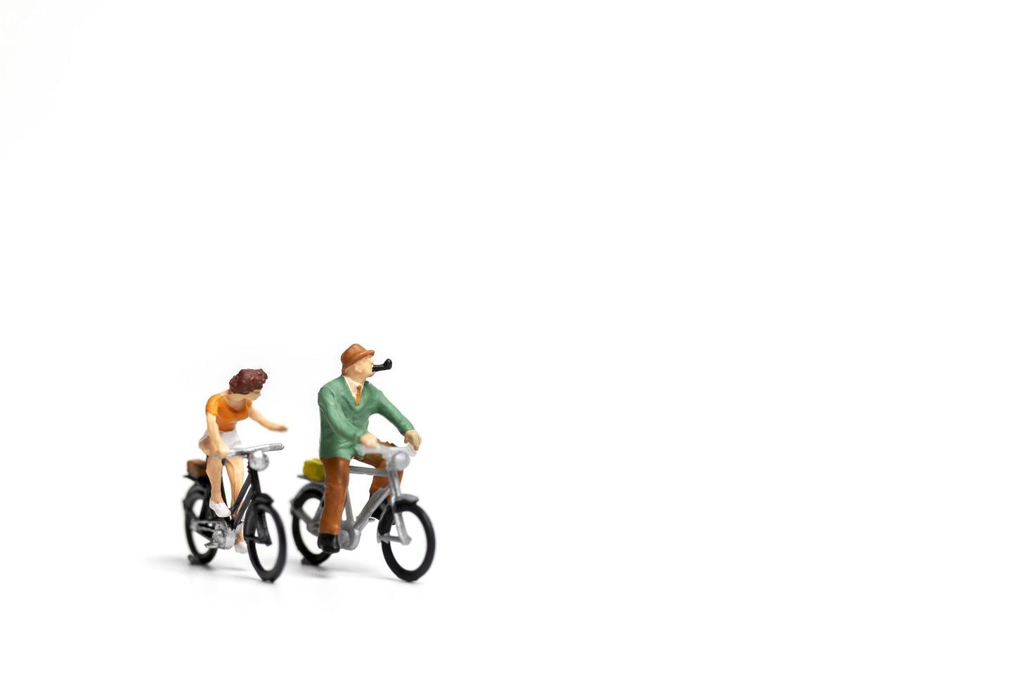 casal em miniatura andando de bicicleta em um fundo branco, conceito do dia dos namorados foto