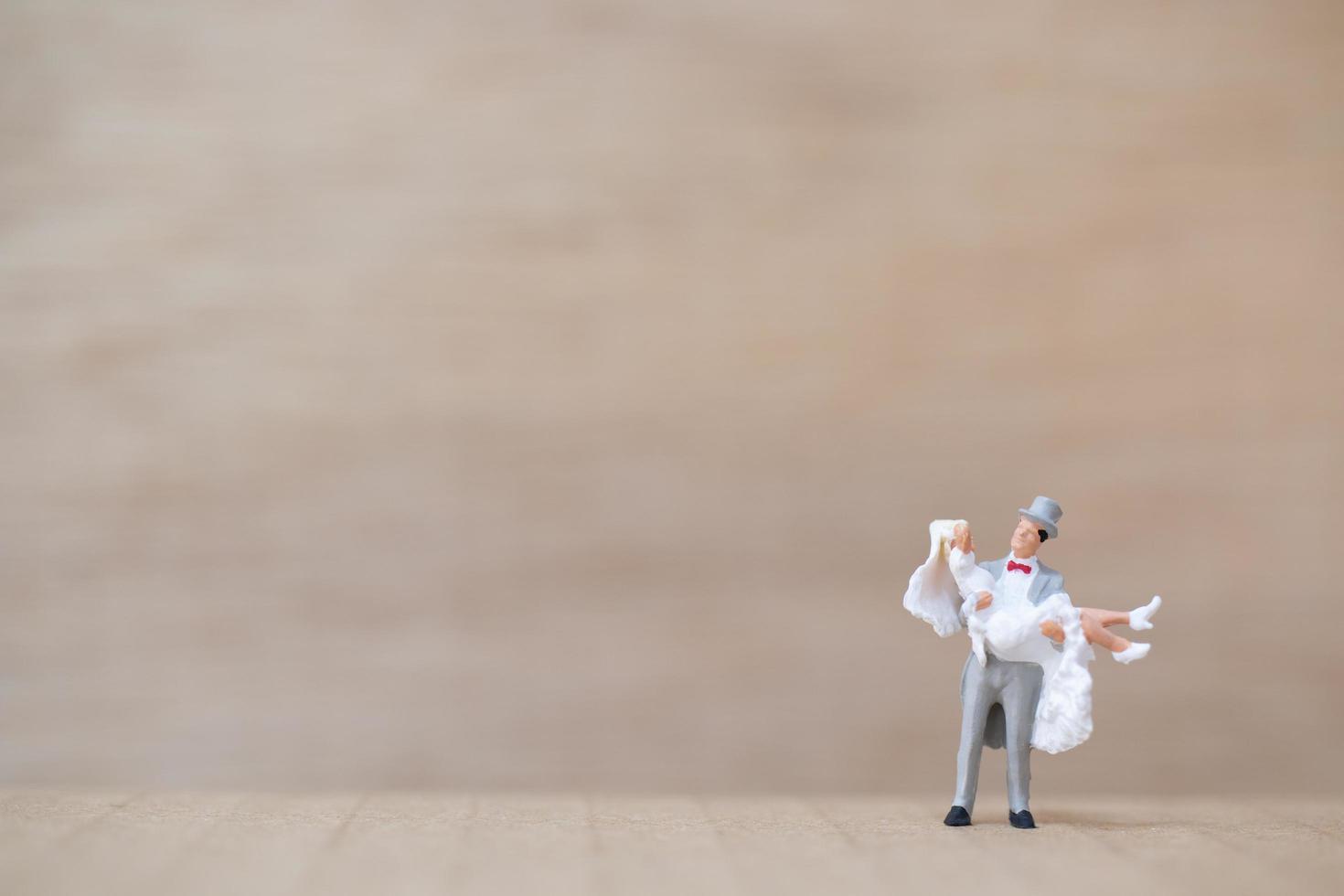noiva e noivo em miniatura em um fundo de madeira foto