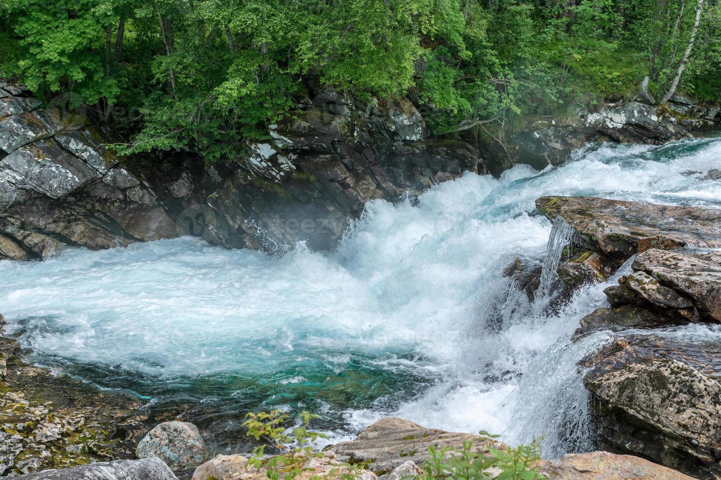 riacho na Noruega com água doce azul-turquesa passando pelas rochas foto