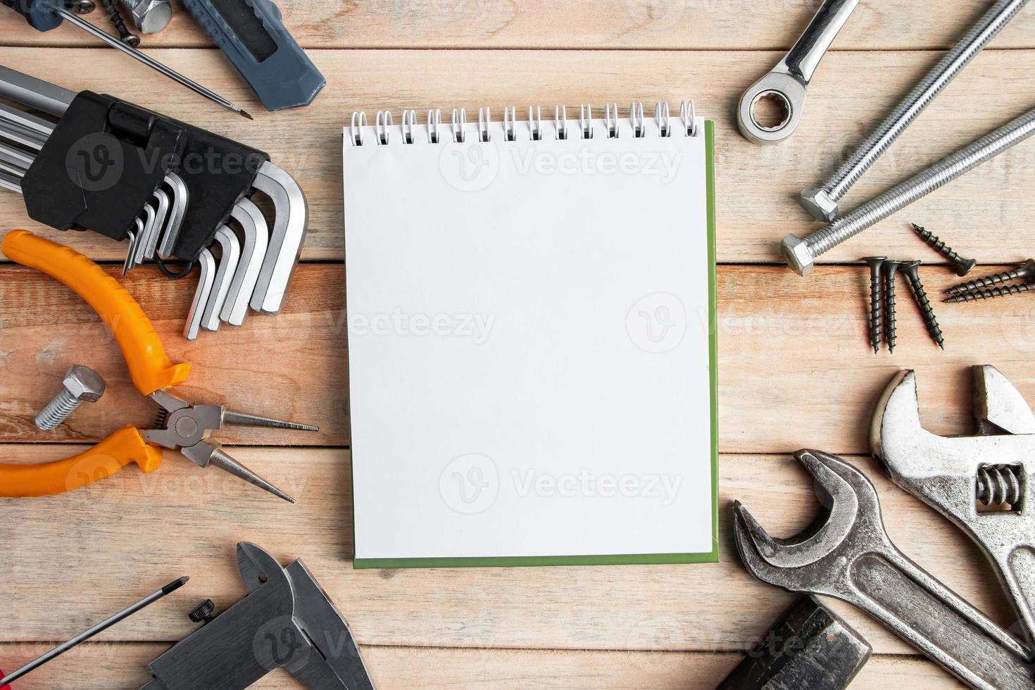 conjunto de ferramentas de trabalho com um bloco de notas em um fundo de madeira foto