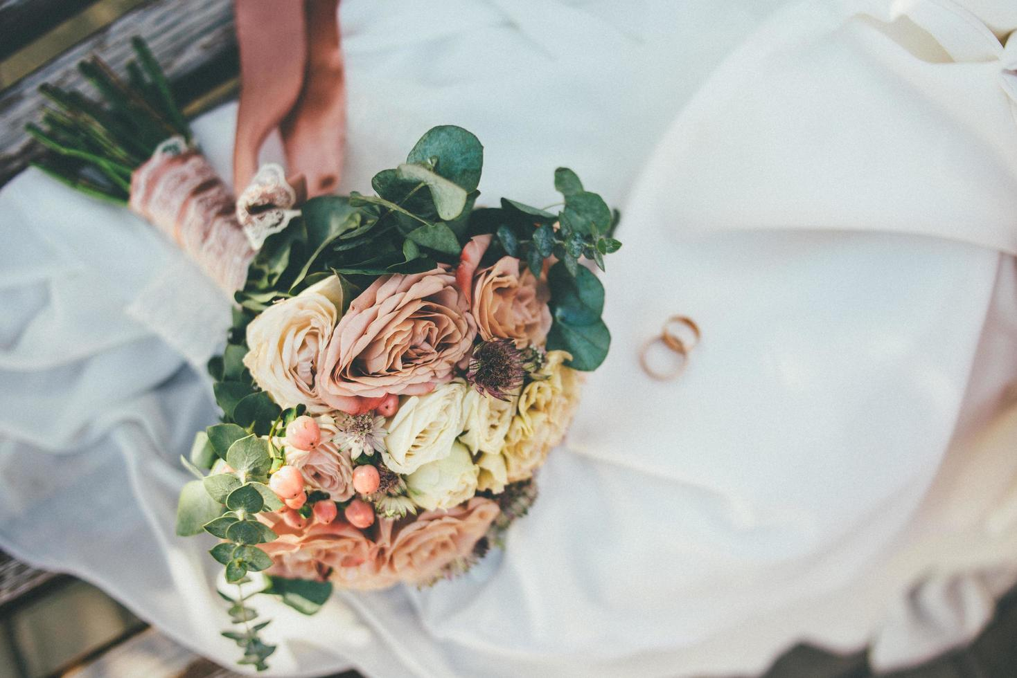buquê de flores e alianças de casamento foto