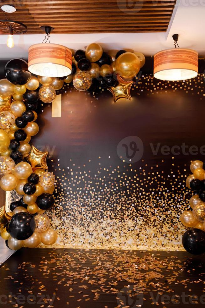 balões dourados e pretos decorados com balões pretos e amarelos. festa elegante com balões. local de celebração. foto