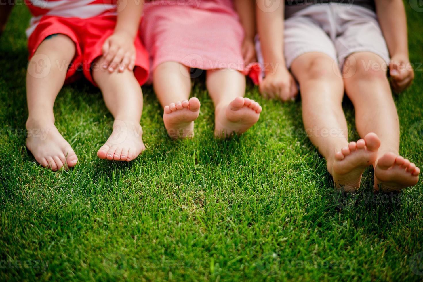 pernas nuas de meninas sentadas na grama. foto