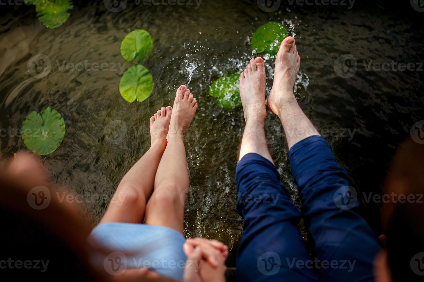 casal espirrando os pés na água ao pôr do sol foto