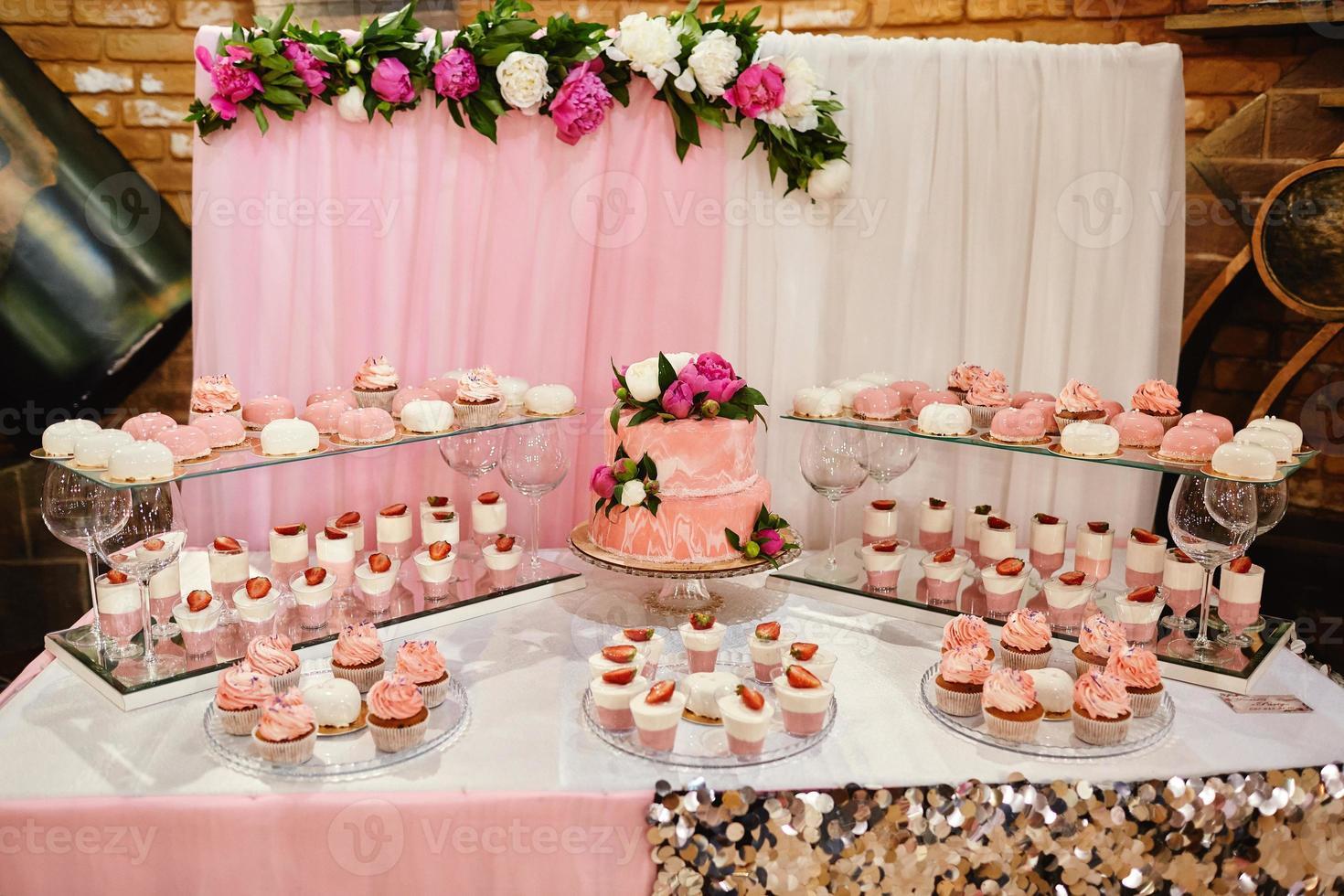 bolos de casamento cor de rosa decorados por flores em uma mesa festiva com sobremesas, tartelete de morango e cupcakes. conceito de casamento foto