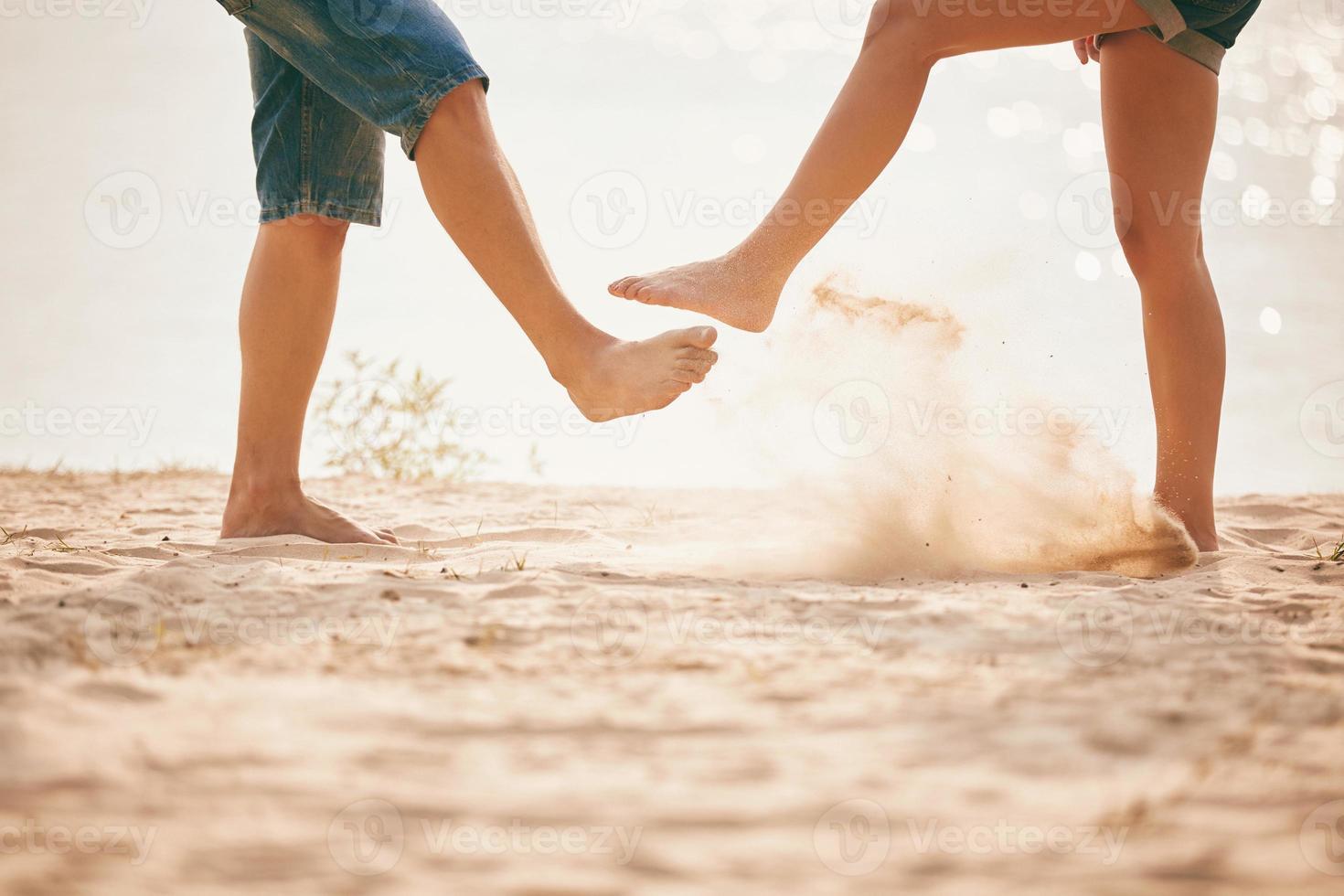 jovem casal brincando com areia. estilo de vida de verão. pés na areia na praia foto