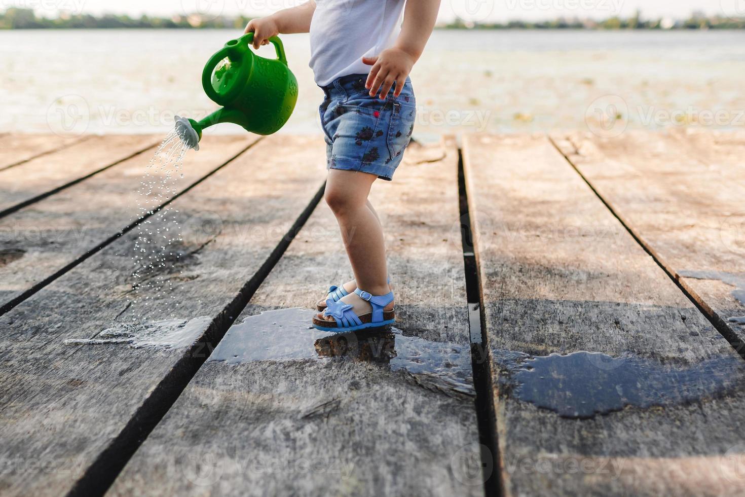 uma menina brincando com um regador de uma ponte de madeira foto