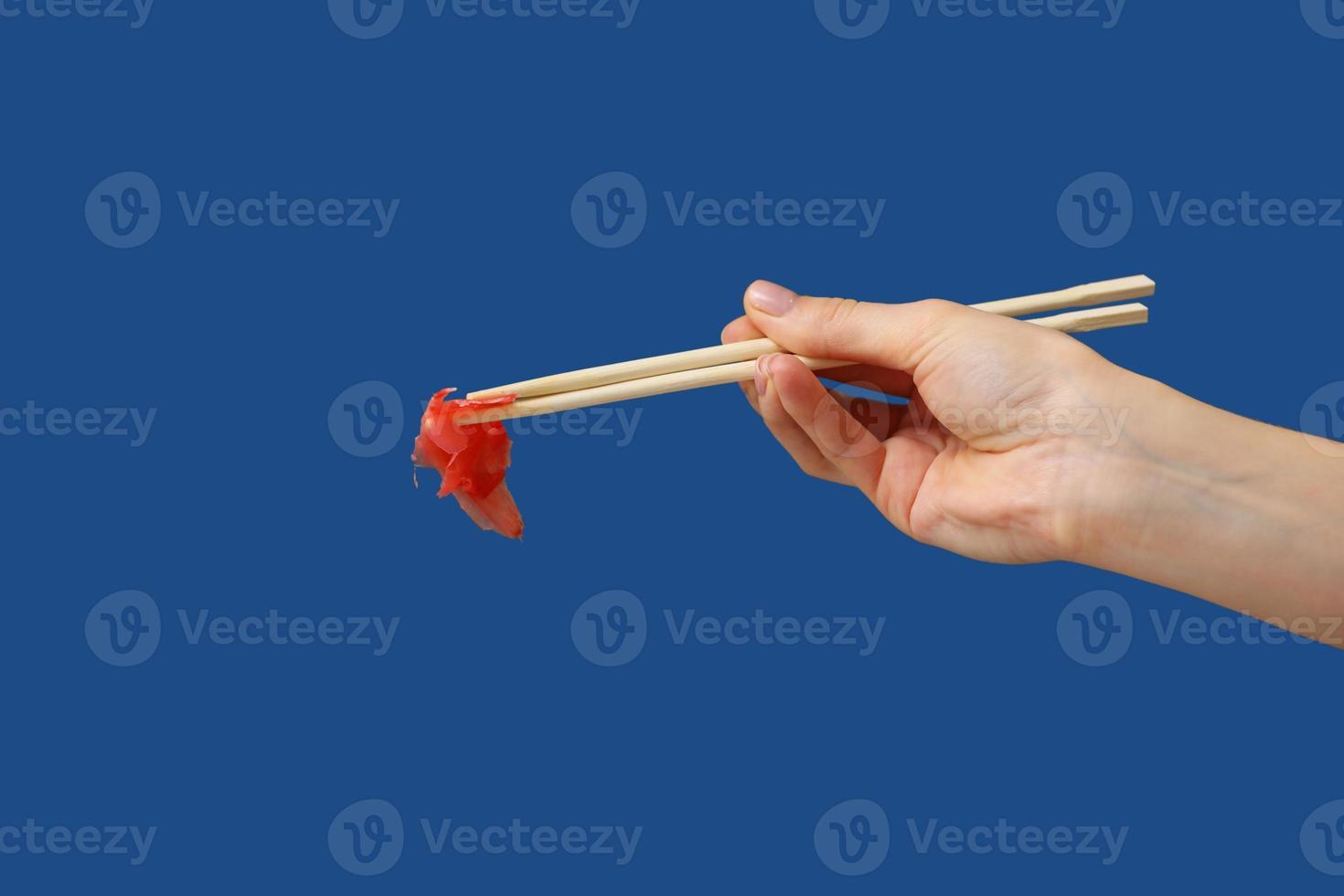 close-up da mão de uma mulher segurando gengibre para sushi com pauzinhos de madeira isolados sobre fundo azul. copie o espaço. foto