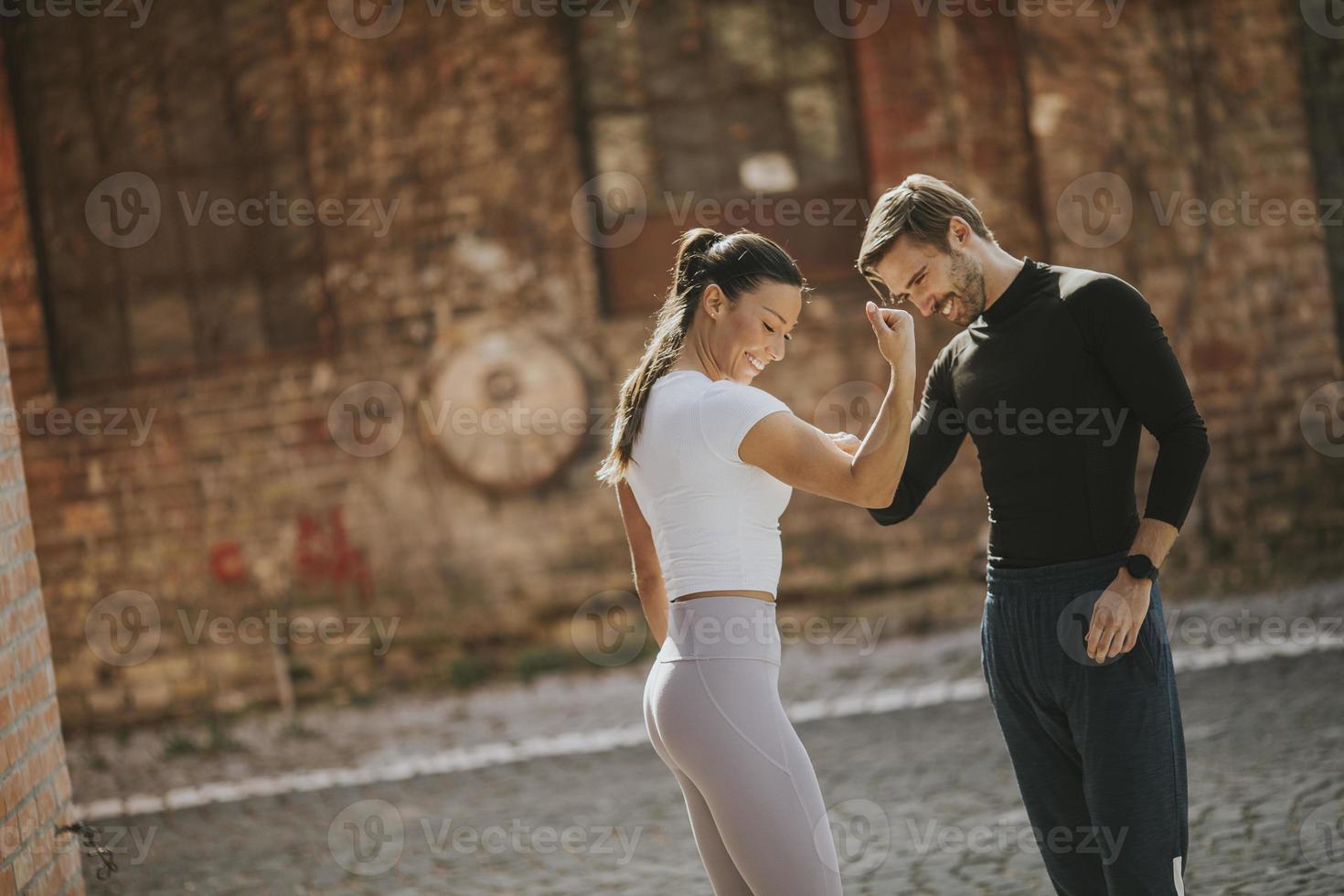 jovem fazendo exercícios de alongamento após correr com seu personal trainer foto