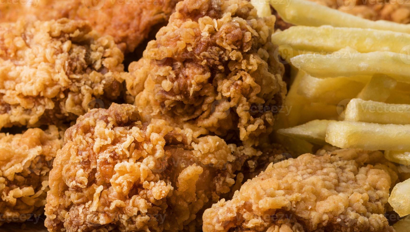 close-up de asas de frango frito com batatas fritas foto