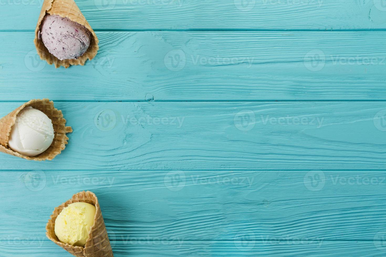 casquinhas de sorvete com sabores diferentes na mesa de madeira azul foto