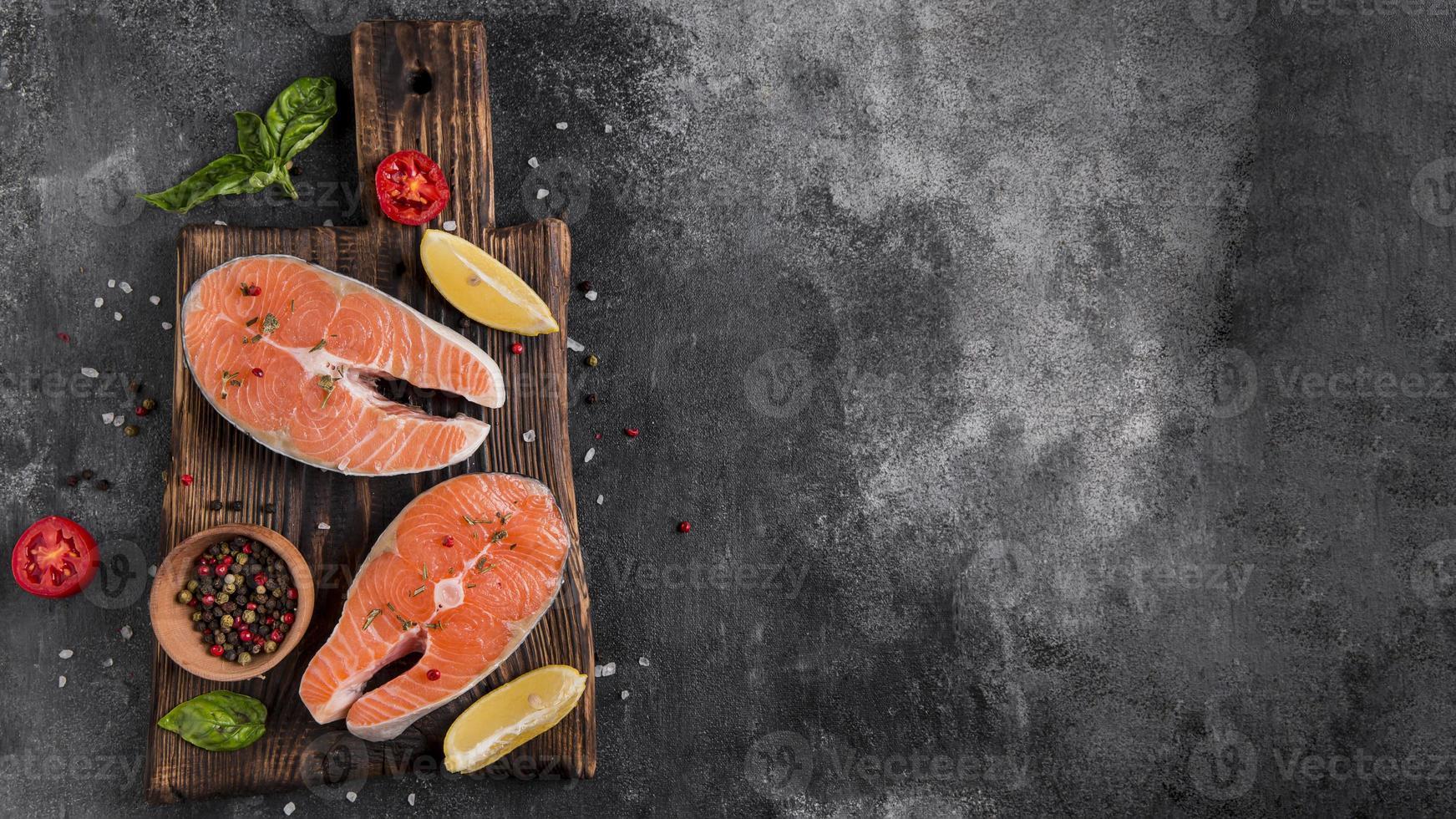 Peixe salmão fresco delicioso em fundo cinza escuro foto