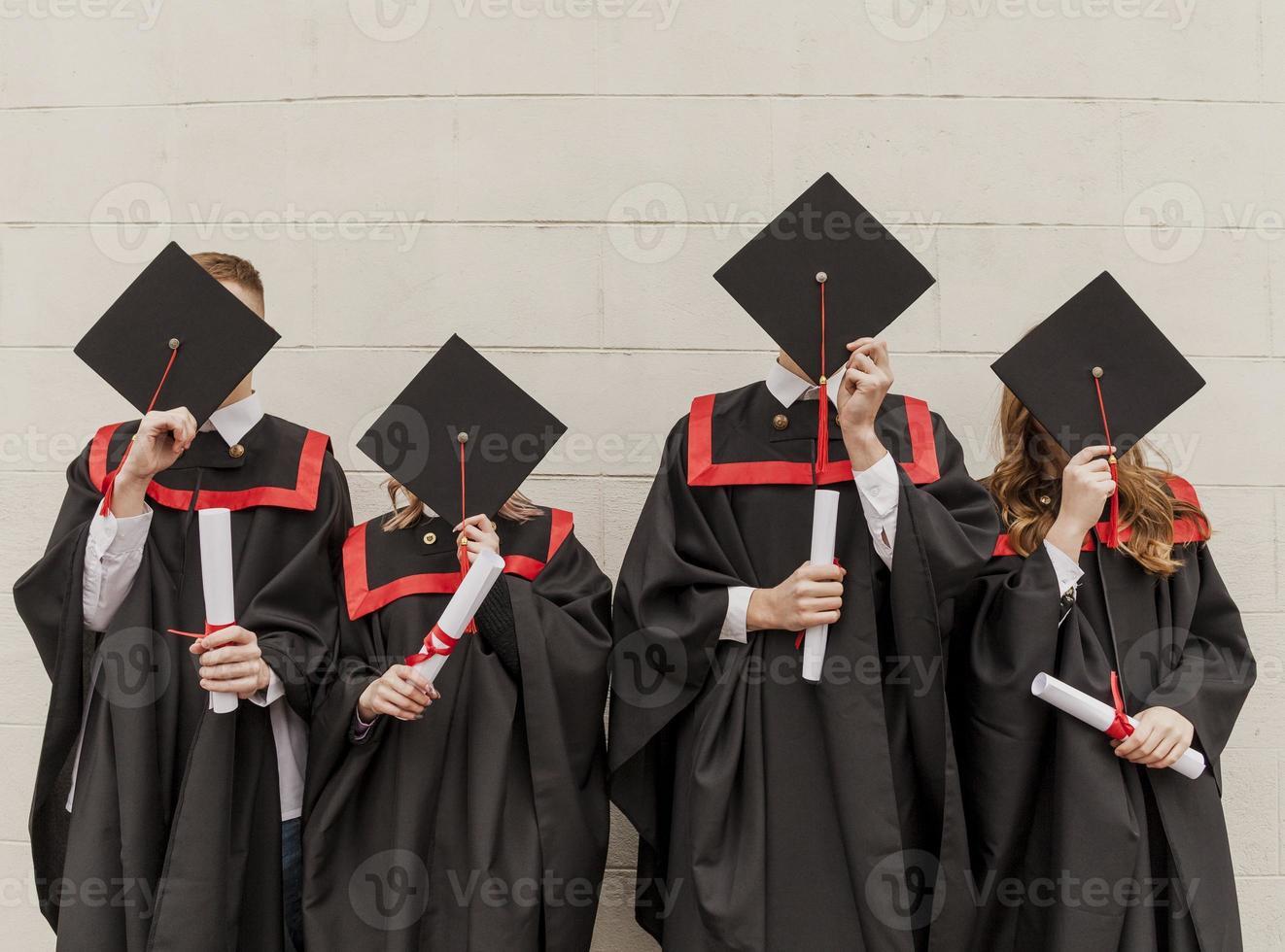 vista frontal de alunos se formando cobrindo rostos foto