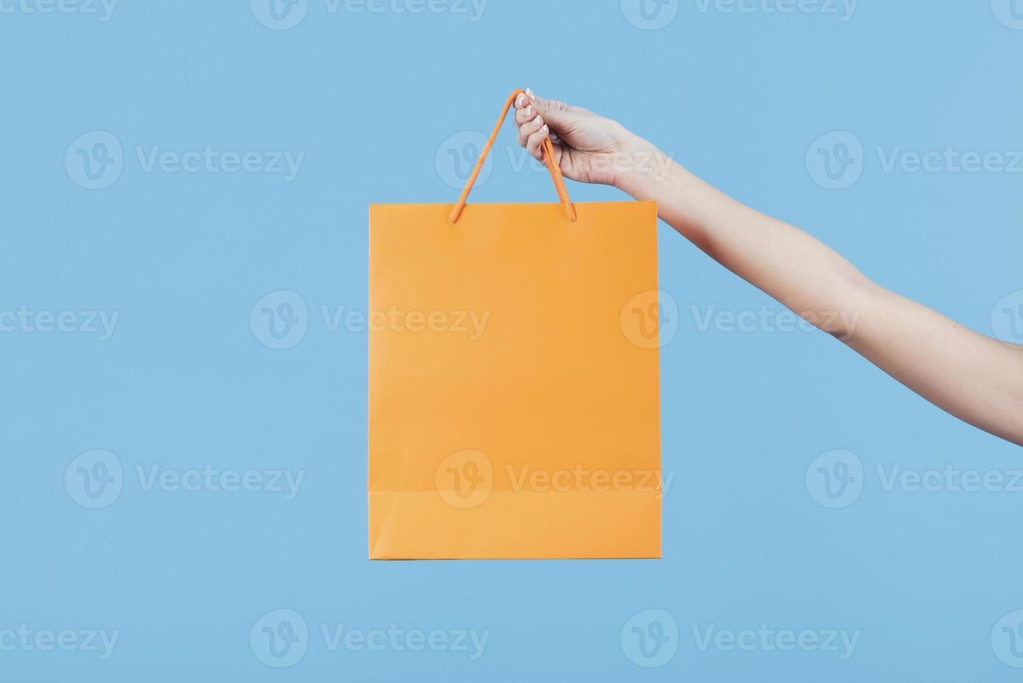 mão segurando uma sacola de compras em um fundo azul claro foto