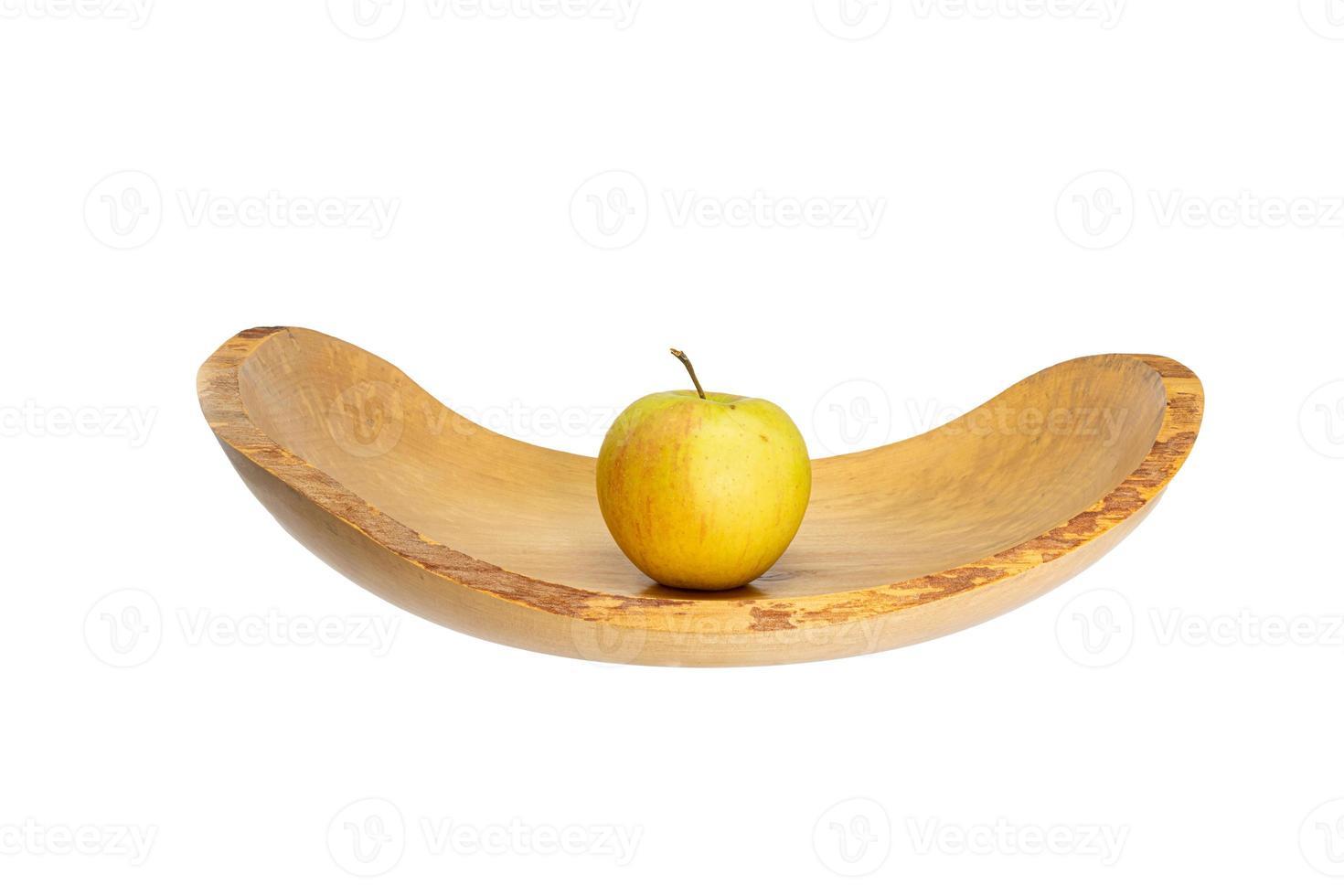vista lateral de uma tigela de madeira plana com uma maçã no meio foto