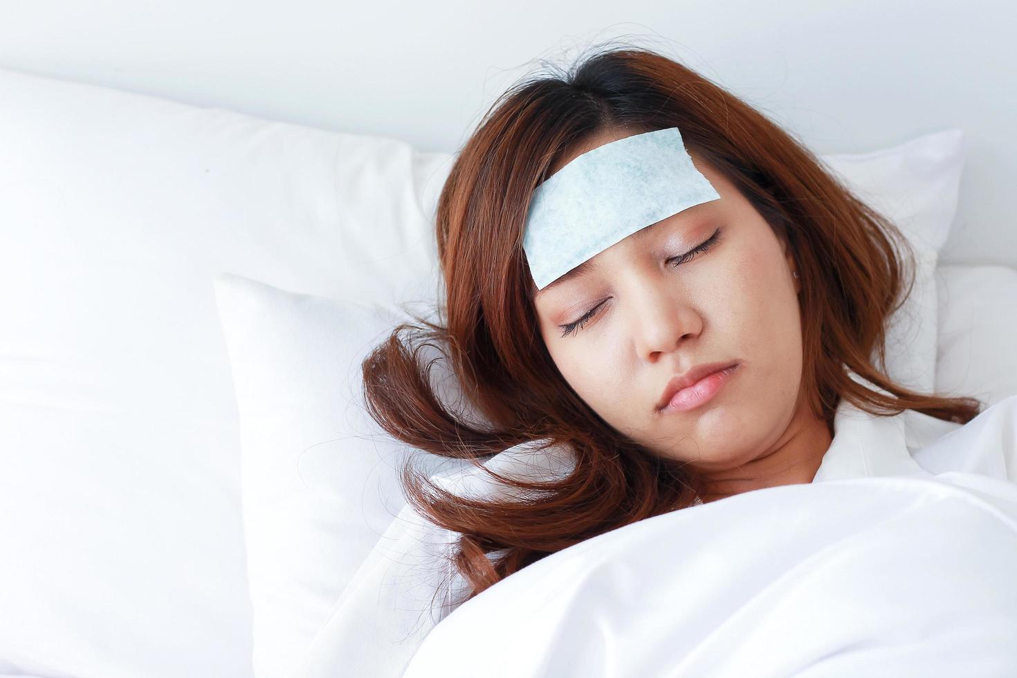 jovem mulher asiática está doente e dormindo na cama. foto