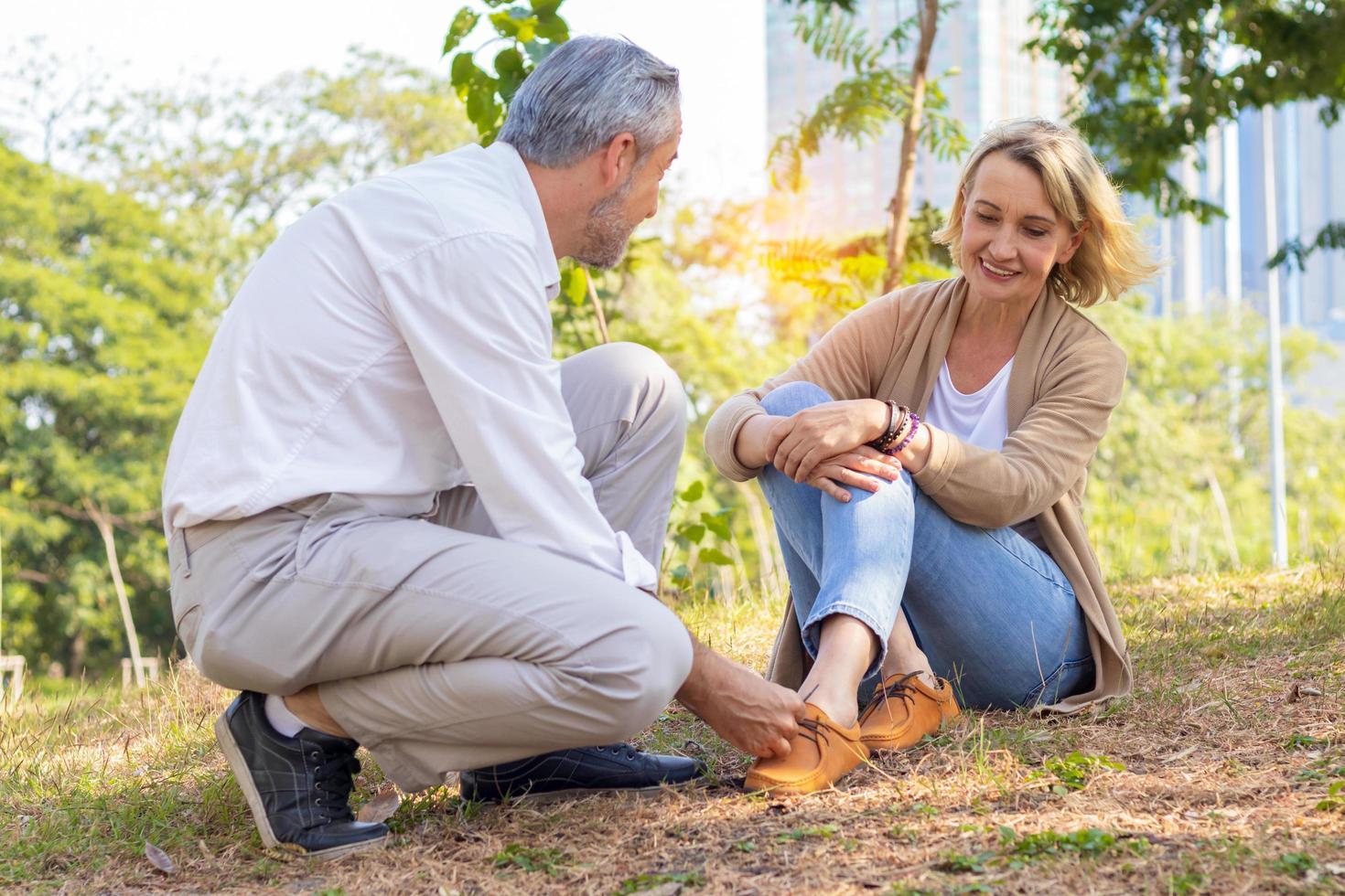 homem amarrar sapatos para mulher. idosos passam as férias no parque felizes na aposentadoria. foto