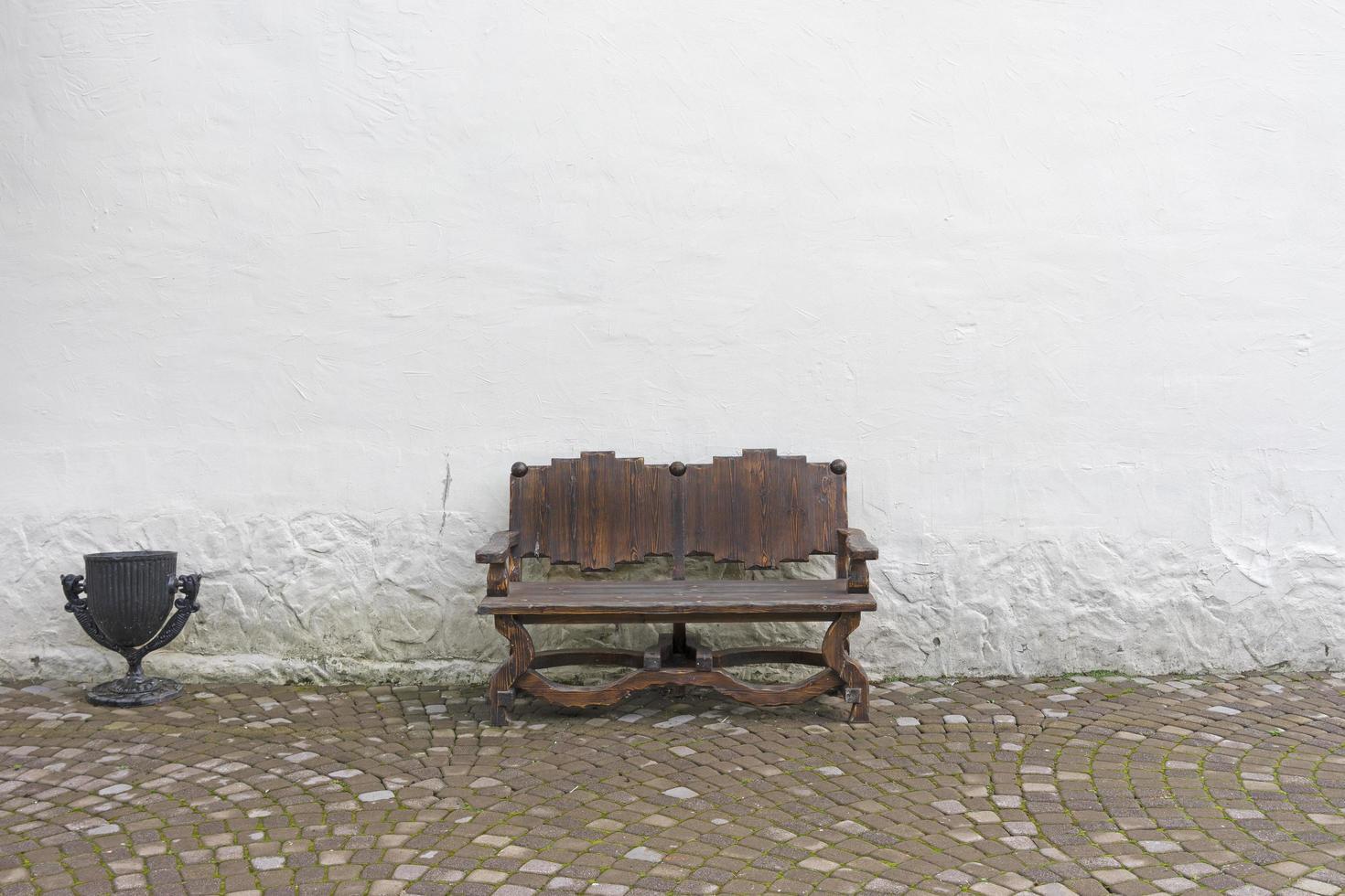 banco de madeira em um fundo de parede branca foto