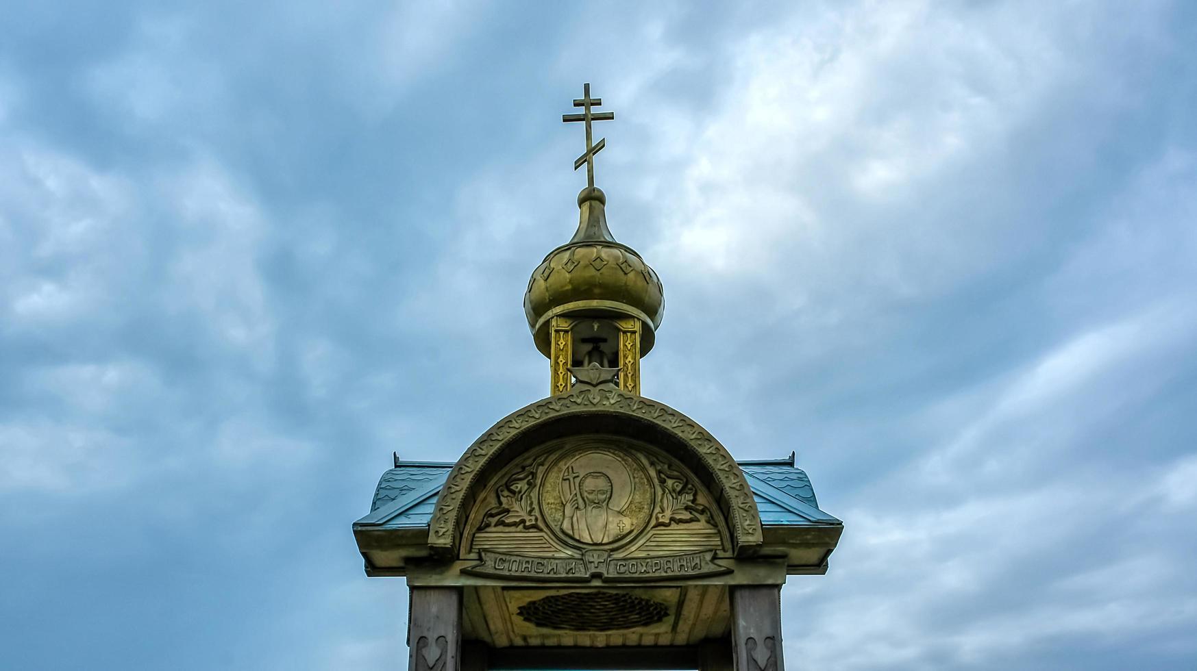 uma capela de madeira no fundo do céu nublado. foto