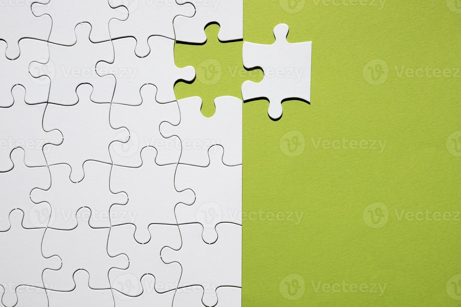 peça de quebra-cabeça branca separada com grade de quebra-cabeça branca em fundo verde foto