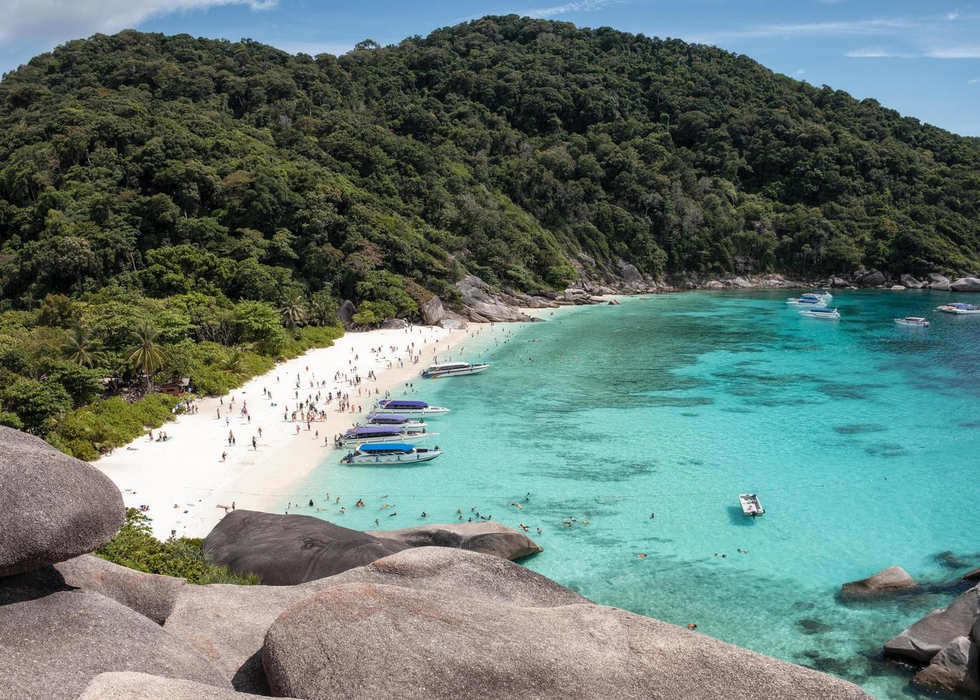 lindo mar tropical com penhasco de pedra e turistas viajando pela ilha de Similan foto