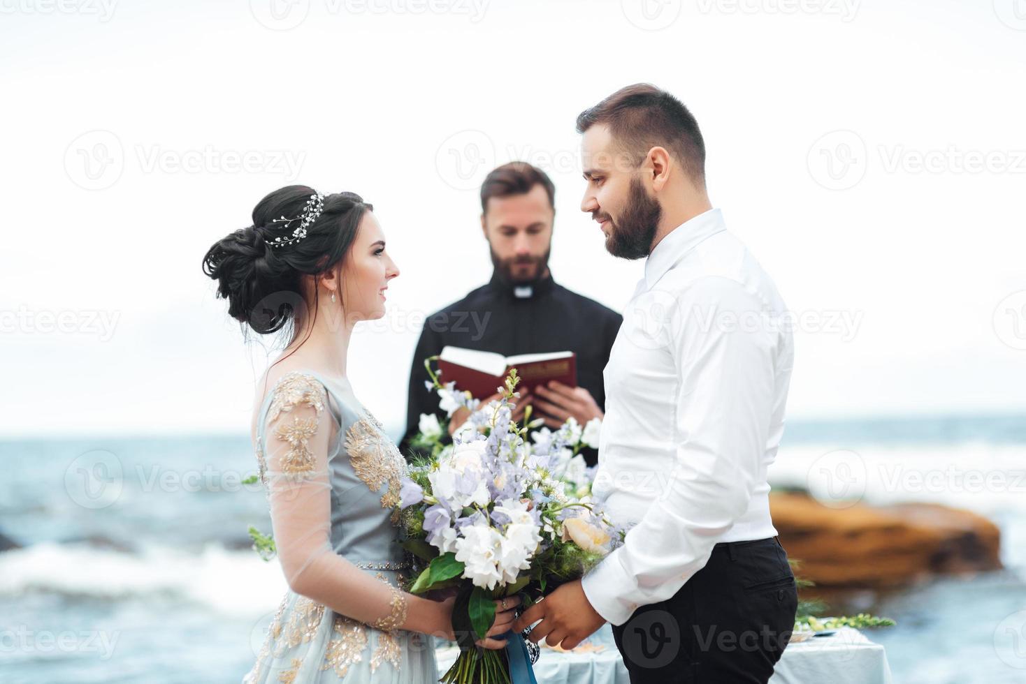 casal de noivos no oceano com um padre foto