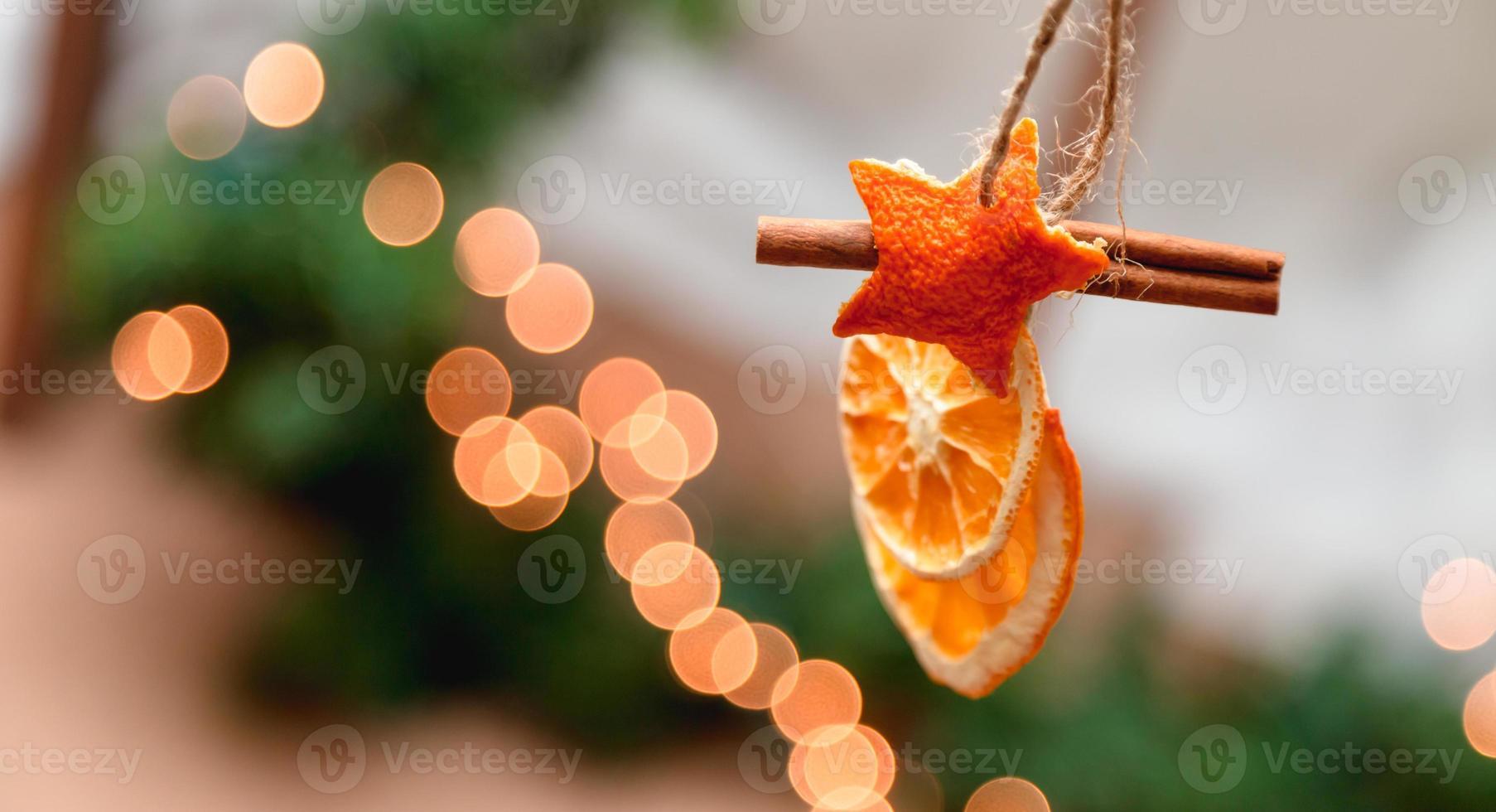 decoração de natal pendurada com laranjas secas, tangerina e estrelas de canela foto