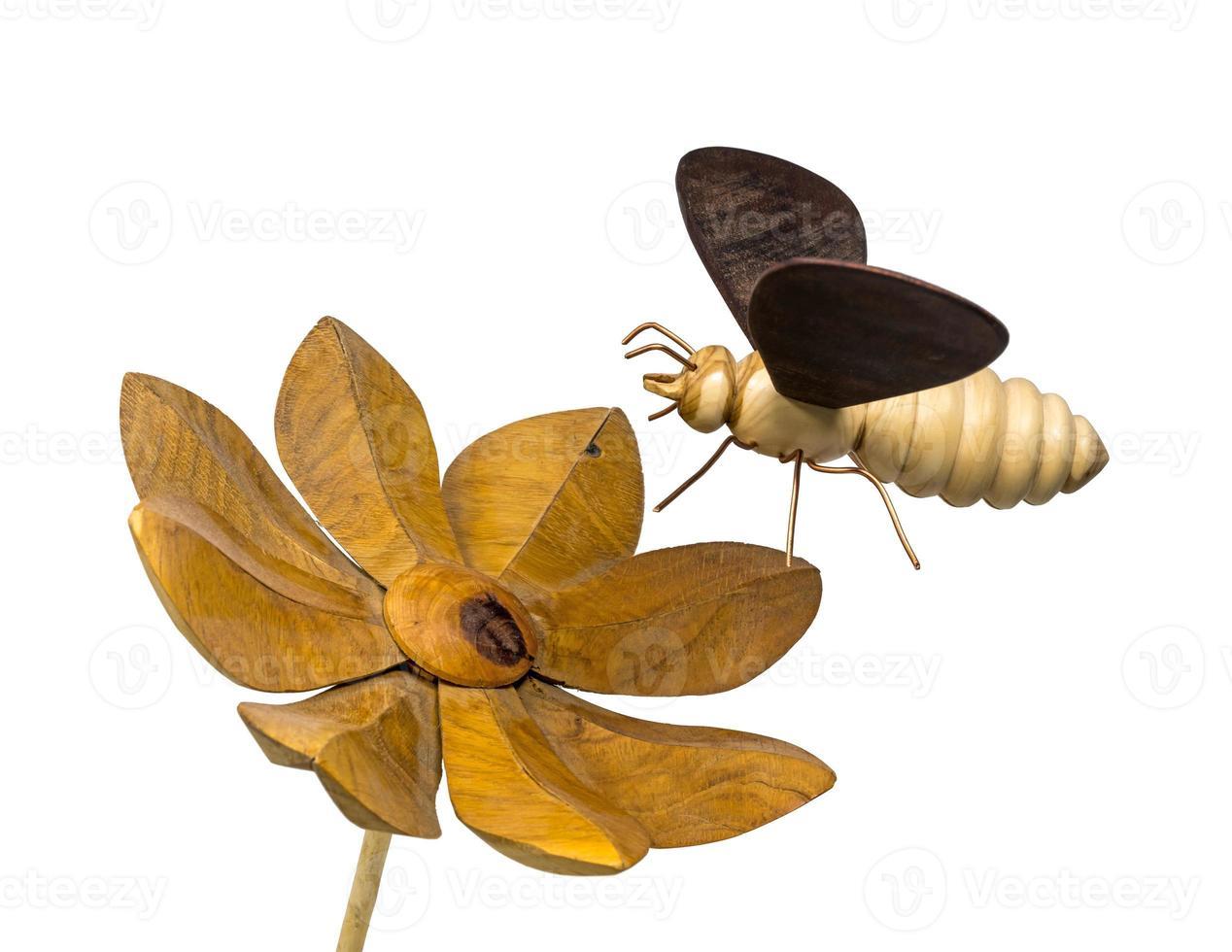 modelo de uma abelha de madeira voa em direção a uma flor de madeira foto