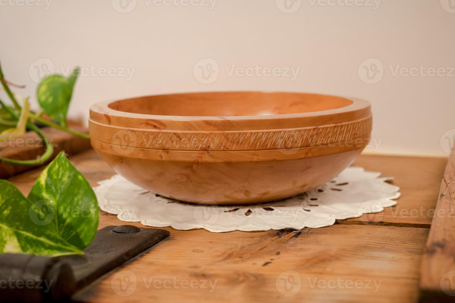 uma tigela de madeira torneada à mão feita de pereira clara com decoração toda redonda está em uma placa de madeira foto