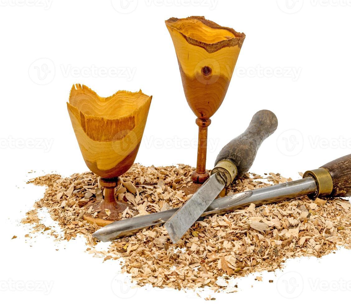 taças de madeira torneadas à mão decoradas com serragem e ferramenta isolada no branco foto